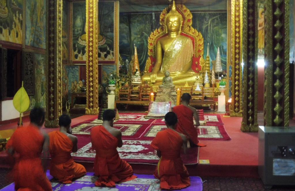Monjes de oración pakse en la noche en un templo